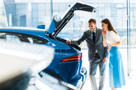 Photo for Selective focus of bearded man and excited woman looking at car trunk - Royalty Free Image