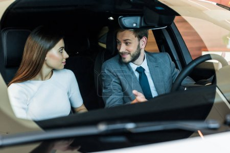 selective focus of bearded man looking at woman in car