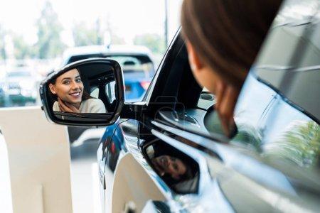 selective focus of happy woman looking at car mirror