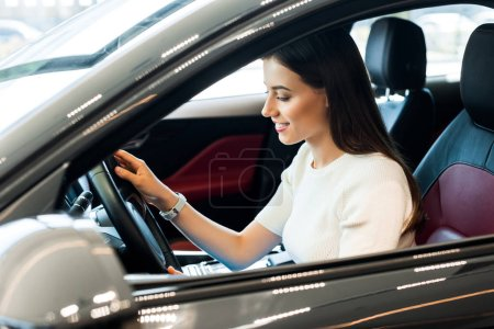 Photo for Selective focus of positive woman touching steering wheel while sitting in car - Royalty Free Image