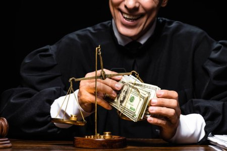 Photo for Cropped view of smiling judge in judicial robe sitting at table and holding dollar banknotes isolated on black - Royalty Free Image