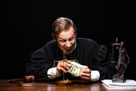 Photo pour Un juge souriant en robe de magistrat assis à table et tenant des billets de dollars isolés sur noir - image libre de droit