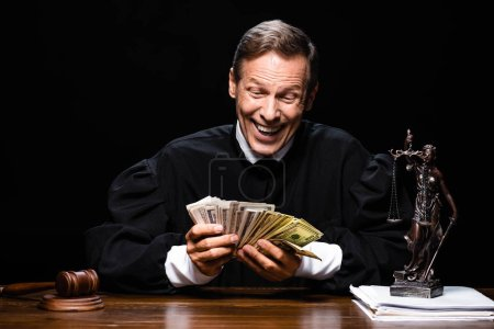 Photo for Smiling judge in judicial robe sitting at table and holding dollar banknotes isolated on black - Royalty Free Image