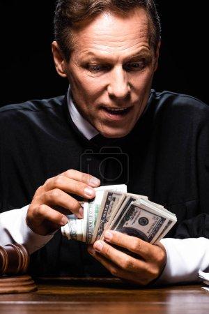 Foto de Juez en la barra judicial sentada a la mesa y recuento de billetes de banco en dólares aislados en negro - Imagen libre de derechos