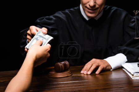 cropped view of woman giving bribe to judge isolated on black
