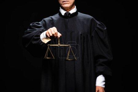 Photo pour Crochet vue d'un juge en robe de juge tenant des échelles de justice isolées sur le noir - image libre de droit
