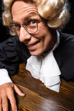 smiling judge in judicial robe and wig sitting at table isolated on black