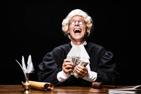 Photo for Smiling judge in judicial robe and wig sitting at table and holding money isolated on black - Royalty Free Image