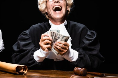 Photo for Cropped view of smiling judge in judicial robe and wig sitting at table and holding money isolated on black - Royalty Free Image