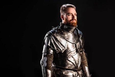 Photo pour Beau chevalier en armure regardant loin isolé sur noir - image libre de droit