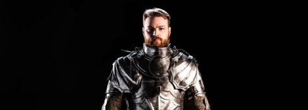 Photo for Panoramic shot of handsome knight in armor isolated on black - Royalty Free Image