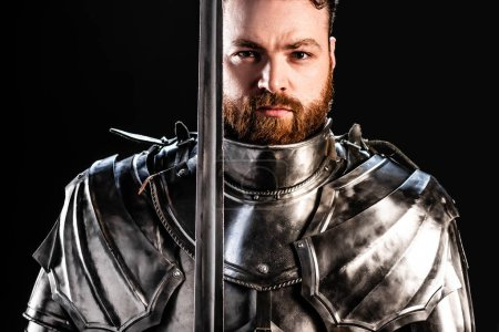 Photo for Handsome knight in armor holding sword isolated on black - Royalty Free Image