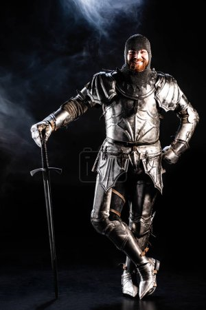 Photo for Smiling knight in armor looking at camera and holding sword on black background - Royalty Free Image