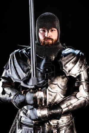 Photo pour Beau chevalier en armure regardant la caméra et tenant l'épée isolée sur noir - image libre de droit
