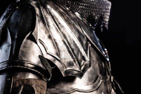 Photo pour Vue recadrée du chevalier en armure tenant l'épée isolée sur noir - image libre de droit