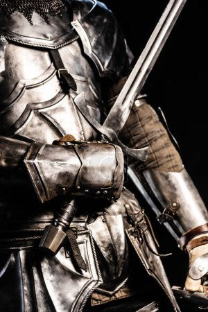 Photo for Cropped view of knight in armor holding sword isolated on black - Royalty Free Image