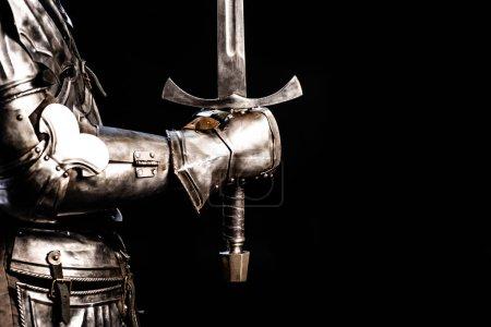 Photo pour Crochet vue de chevalier en armure tenant épée isolée sur noir - image libre de droit