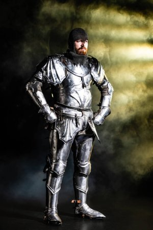 Photo for Handsome knight in armor looking away with hands on hips on black background - Royalty Free Image