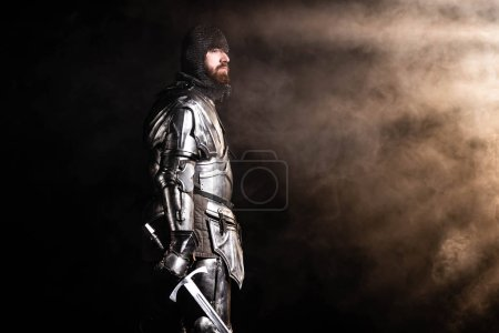 Photo for Handsome knight in armor holding sword on black background - Royalty Free Image