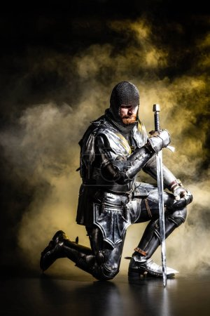 Photo for Handsome knight in armor holding sword and bend knee on black background - Royalty Free Image