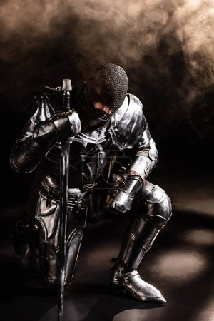 Photo pour Beau chevalier en armure tenant épée et genou plié sur fond noir - image libre de droit