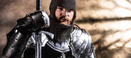 Photo pour Photo panoramique d'un beau chevalier en armure tenant une épée sur fond noir - image libre de droit