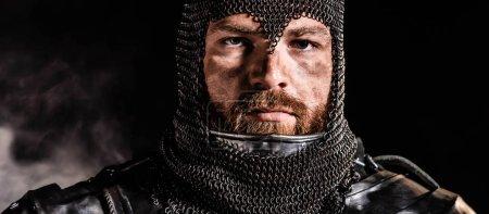 Photo pour Photo panoramique d'un beau chevalier en armure regardant la caméra sur fond noir - image libre de droit