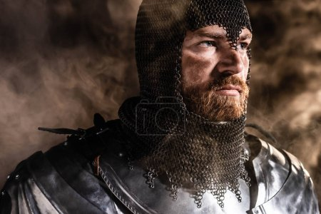 Photo for Handsome knight in armor looking away on black background - Royalty Free Image