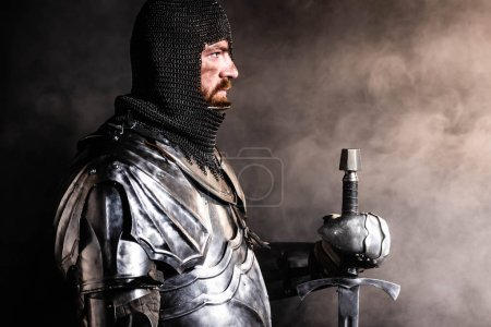 Photo for Side view of handsome knight in armor holding sword on black background - Royalty Free Image