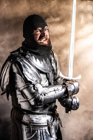 Photo for Handsome knight in armor holding sword and fighting on black background - Royalty Free Image
