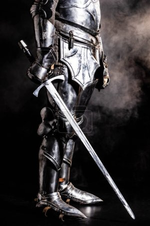 Photo for Cropped view of knight in armor holding sword on black background - Royalty Free Image