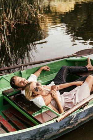 Photo pour Heureux jeune couple se détendre en bateau sur le lac et sourire à la caméra - image libre de droit