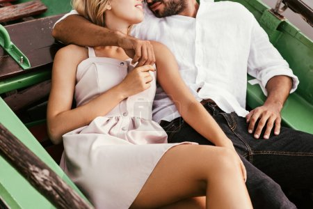 Photo pour Voir un jeune couple souriant se regarder pendant qu'il est assis à bord d'un bateau - image libre de droit