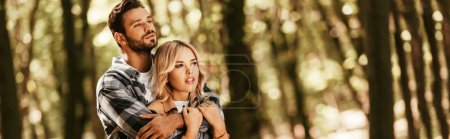 Photo for Panoramic shot of happy man embracing attractive girlfriend while looking away in park - Royalty Free Image