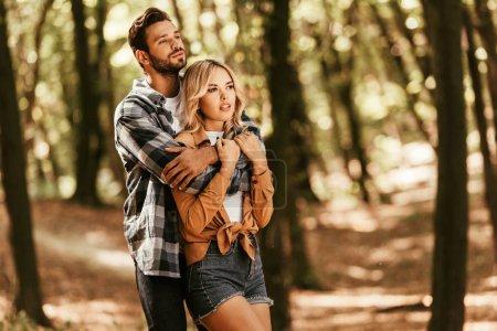 Photo pour Bel homme embrassant sa petite amie rêveuse tout en regardant ailleurs dans le parc - image libre de droit