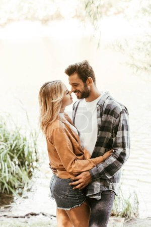 Photo for Happy young couple smiling and hugging near lake in park - Royalty Free Image