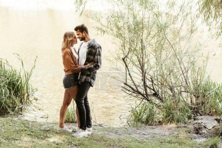 Photo pour Joyeux jeune couple embrassant debout près d'un lac dans le parc - image libre de droit