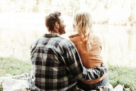 Photo pour Retour vue d'un jeune homme embrassant sa petite amie assise près d'un lac dans le parc - image libre de droit