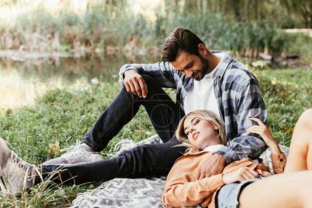 Foto de Guapo hombre abrazando novia durmiendo en la manta cerca del lago en parque. - Imagen libre de derechos