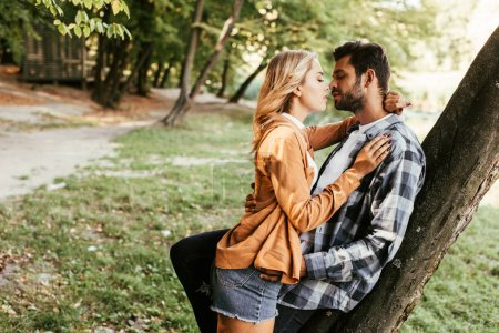 Photo for Attractive young woman kissing boyfriend while standing tree trunk in park - Royalty Free Image