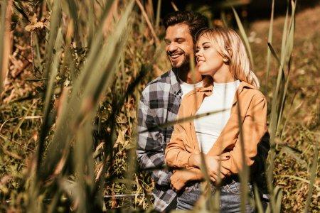 Photo pour Foyer sélectif de jeune homme heureux embrassant petite amie souriante dans le fourré de carex - image libre de droit