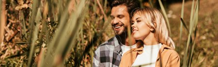 selective focus of happy young couple smiling in thicket of sedge, panoramic shot