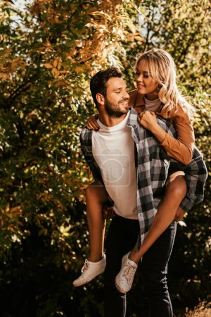 Photo for Handsome, cheerful man piggybacking happy girlfriend in park - Royalty Free Image