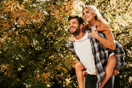 Photo for Happy young man piggybacking happy girlfriend in park - Royalty Free Image