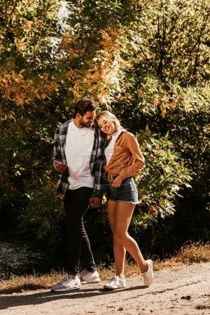 Photo pour Jeune femme heureuse appuyée sur l'épaule du petit ami tout en marchant dans le parc - image libre de droit