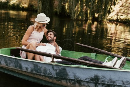 Photo for Young woman in sundress and hat hugging happy boyfriend while sitting in boat - Royalty Free Image