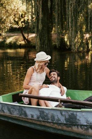 mujer joven en vestido de sol y sombrero abrazando novio feliz mientras está sentado en el barco en el lago