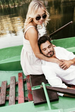 Photo for Attractive woman in sunglasses hugging boyfriend while sitting in boat on lake - Royalty Free Image