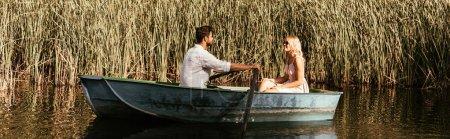 Photo pour Photo panoramique d'un jeune couple en bateau sur la rivière près d'un taillis de carex - image libre de droit