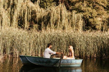 Photo pour Un jeune couple en bateau sur la rivière près d'un bosquet de carex - image libre de droit